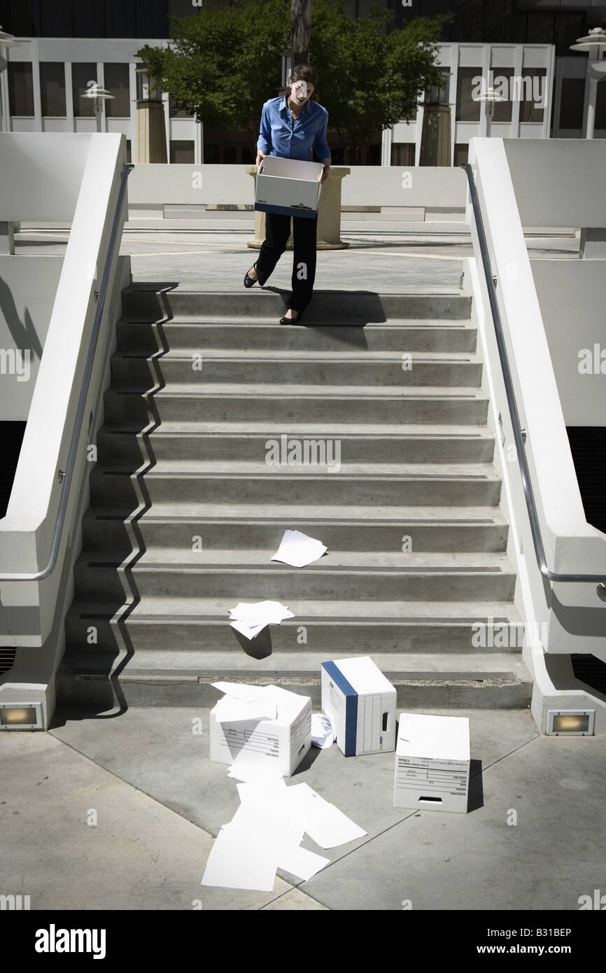 Girl Friday watching boxes of paperwork drop down steps - Stock Image