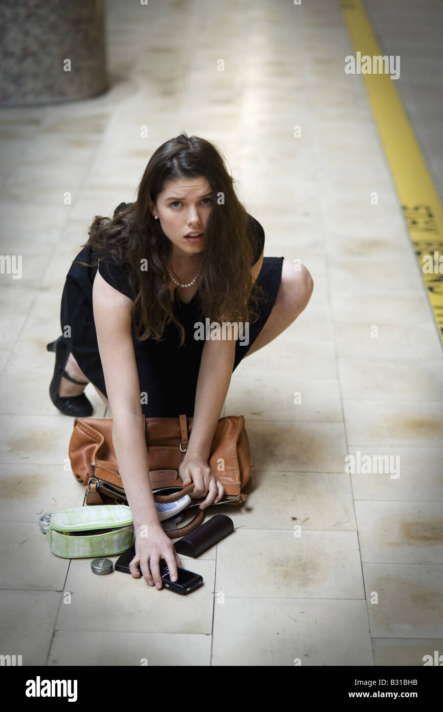 Young woman picking up spilled personal items from the floor - Stock Image