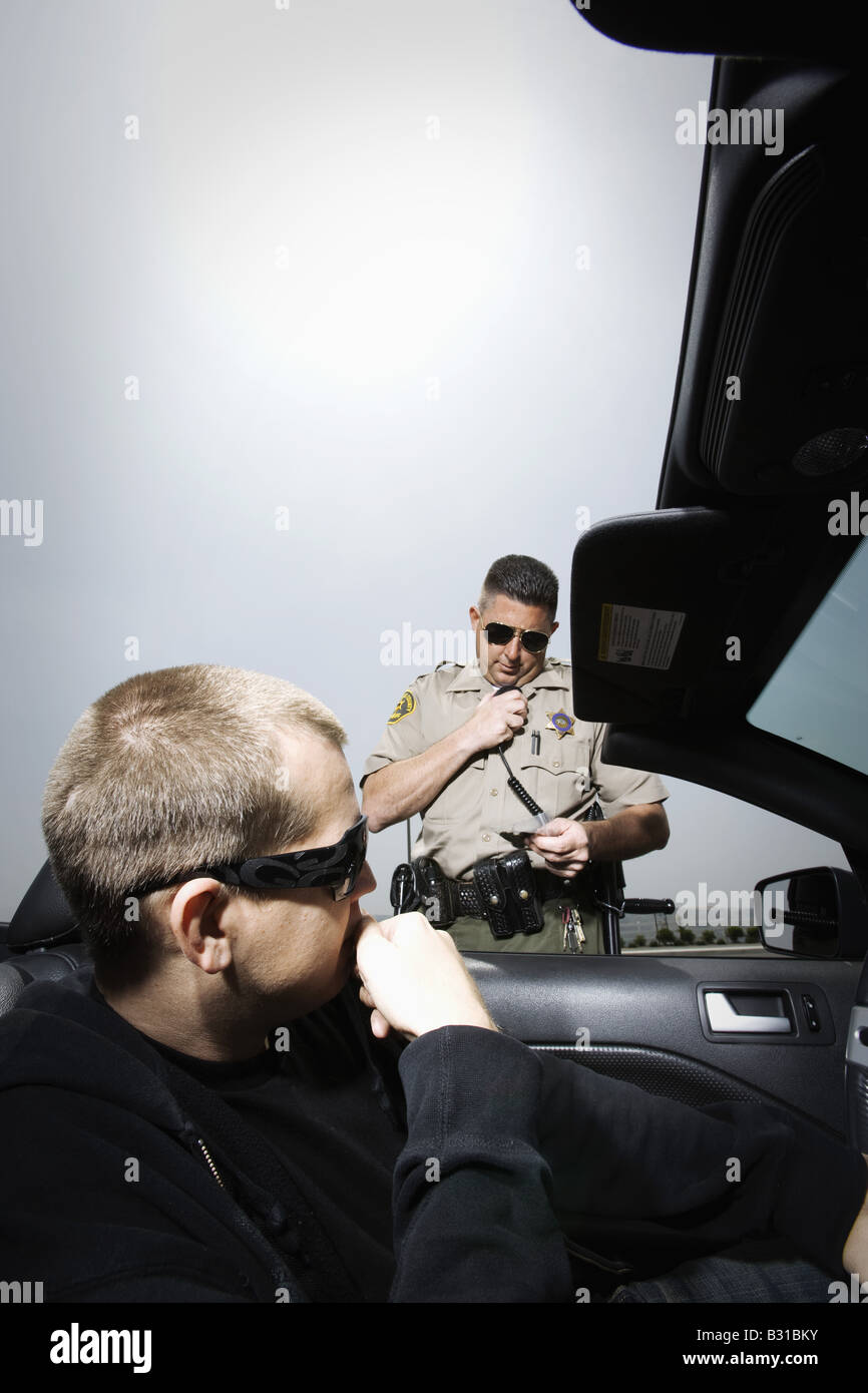 Police officer calling in possession of drugs - Stock Image