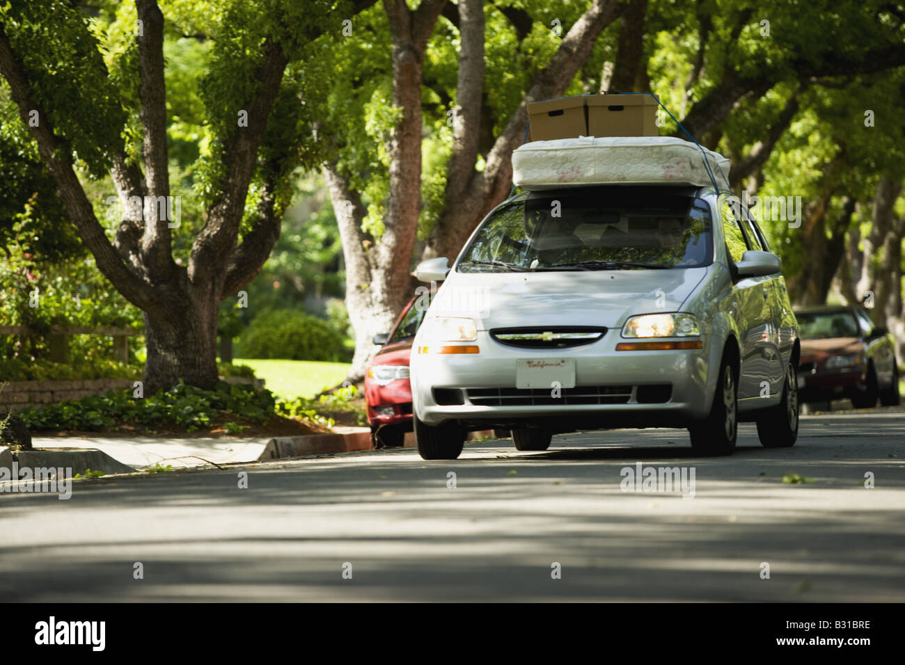 Chevy Aveo driving down tree lined street with mattress and boxes on roof Stock Photo