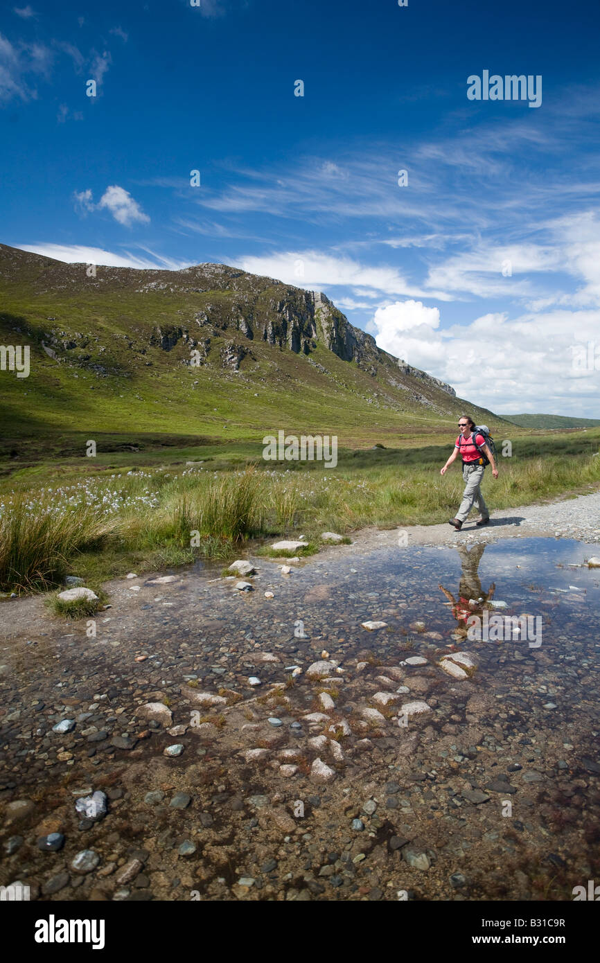 Walker passing a pool on the Trassey Track, beneath Spelack mountain. Mourne Mountains, County Down, Northern Ireland, - Stock Image