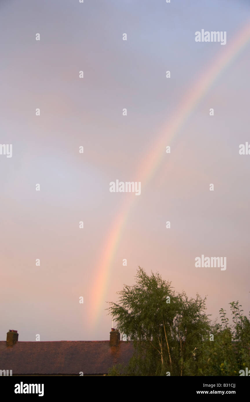 Rainbow and house rooftops - Stock Image