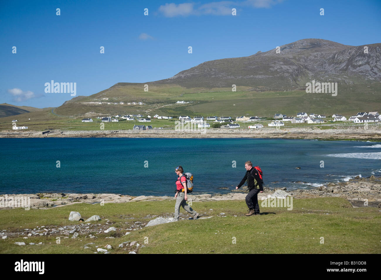 Walkers above Dooagh Bay, Achill Island, County Mayo, Ireland. - Stock Image