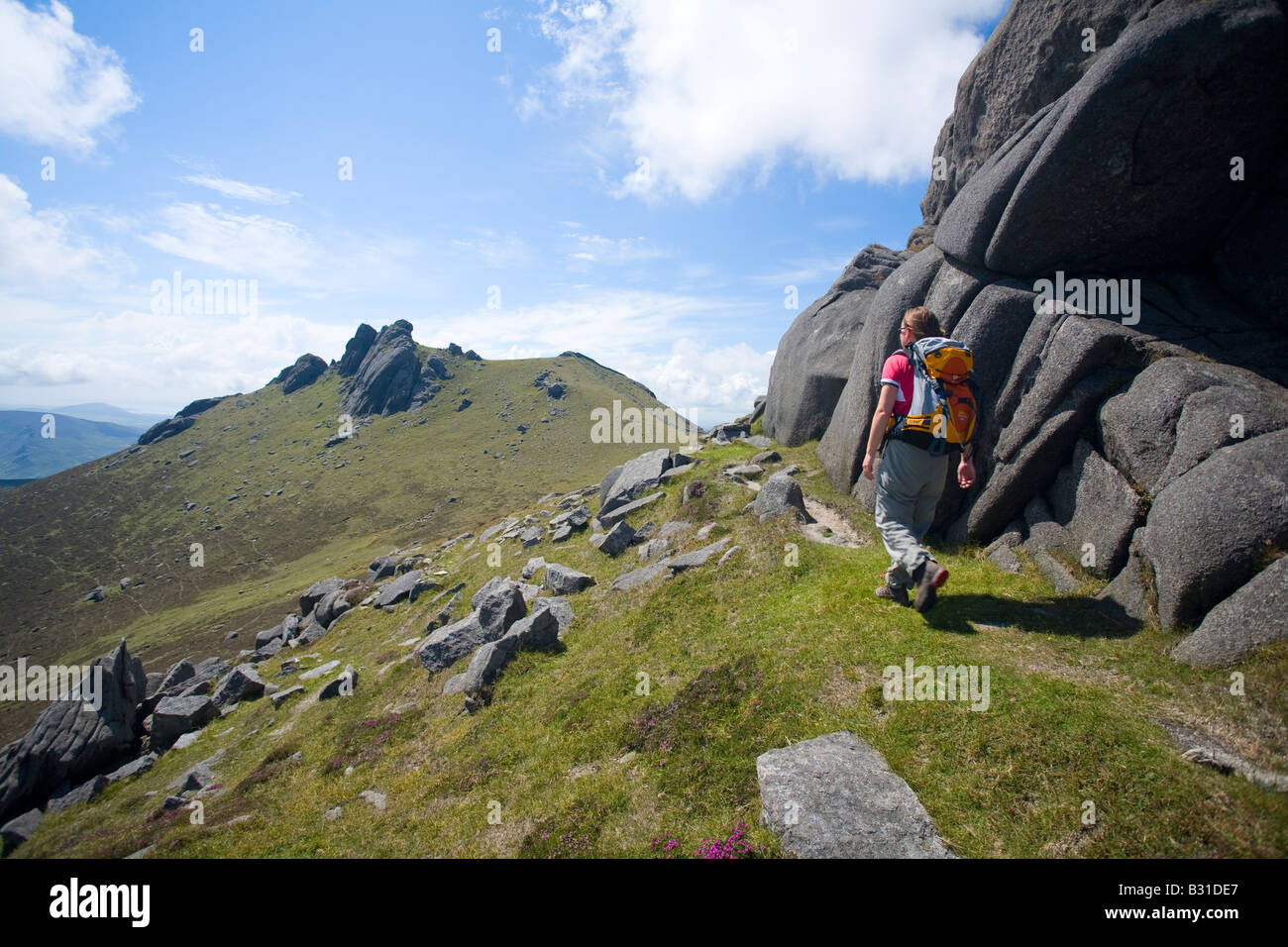 Walker passing the North Tor of Slieve Bearnagh, Mourne Mountains, County Down, Northern Ireland, UK. - Stock Image