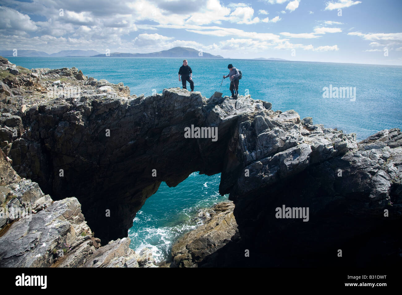 Hikers standing on top of a sea arch at Dooega Head, Achill Island, County Mayo, Ireland. - Stock Image