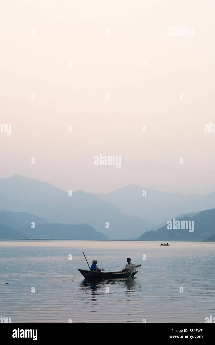 Sunset over Fewa lake with fishing boats. Pokhara, Nepal - Stock Image
