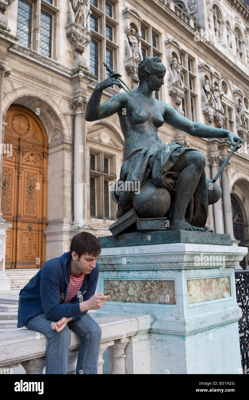 France, Paris, town hall Hotel de Ville young man playing with his mobile phone - Stock Image