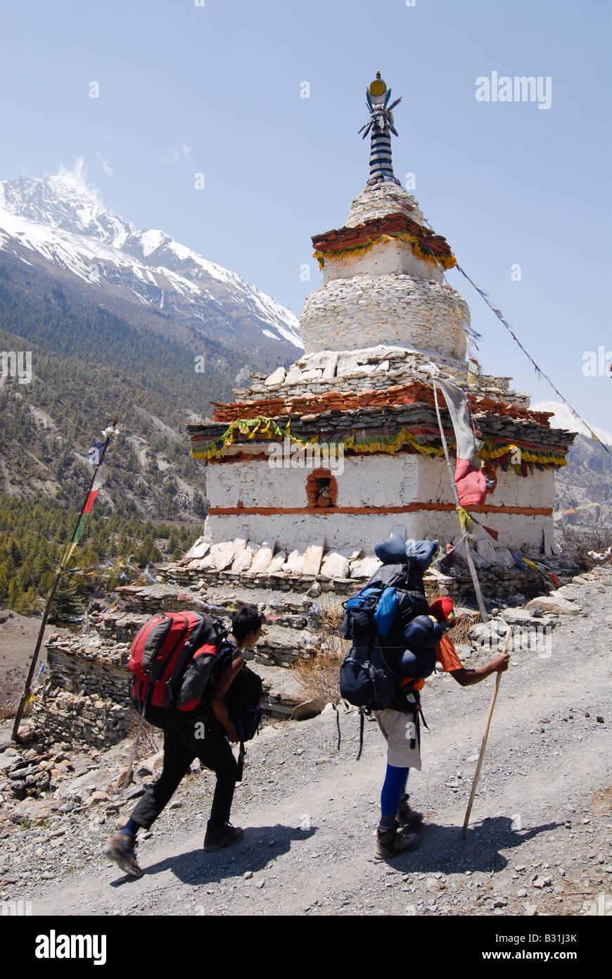 Two trekkers walk past a buddhist stupa on the Annapurana curcuit, Himalaya trekking, Nepal - Stock Image