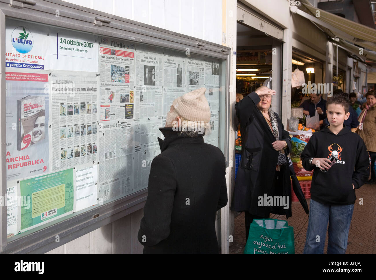 Man reading the leftist newspaper L Unita on display outside the covered market in Ventimiglia - Stock Image