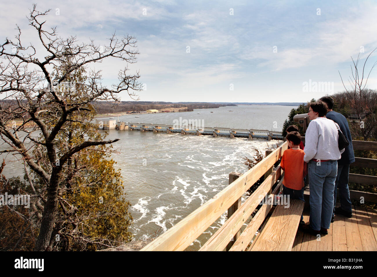 FAMILY LOOKING AT THE HYDROELECTRIC POWER PLANT ON ILLINOIS RIVER FROM A VIEWING PLATFORM IN STARVED ROCK STATE - Stock Image