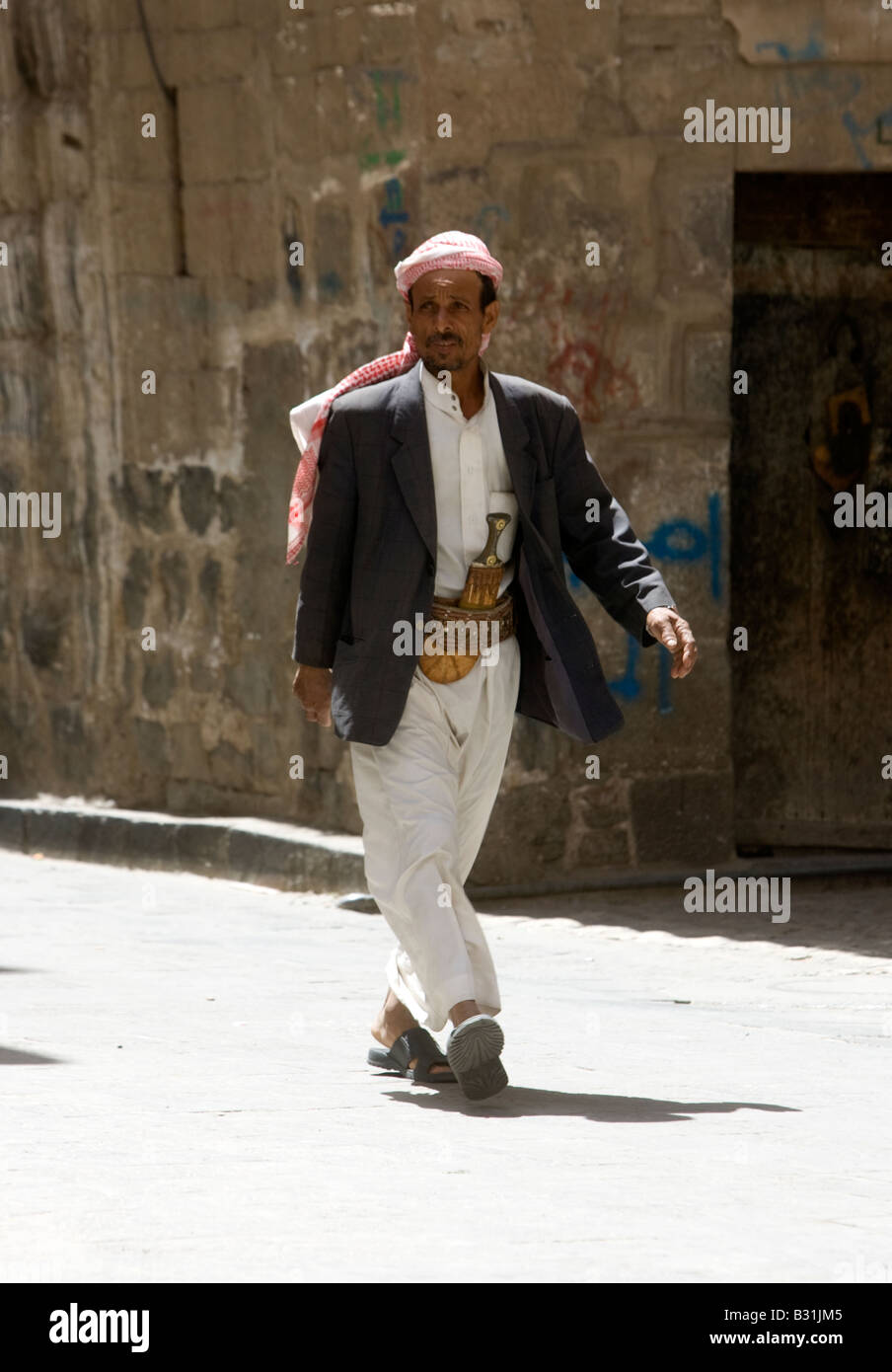A old Muslim man from Yemen walking through Old Sanaa City wearing his traditional Jambiya dagger - Stock Image