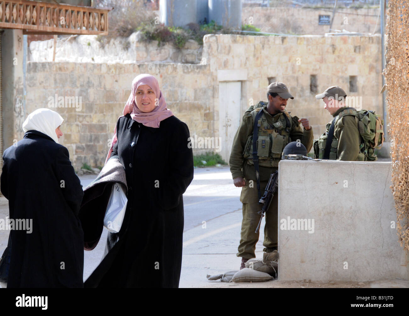 Two Arab women approach a small checkpoint of two Israeli soldiers- one a Russian immigrant and one an Ethiopian - Stock Image