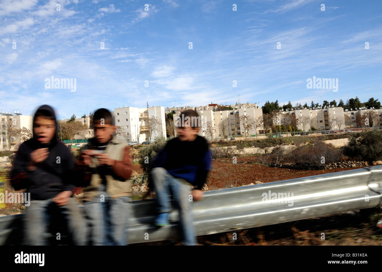 Three Palestinian children sit by the side of a major road in the West Bank- in the Gush Etzion region. - Stock Image