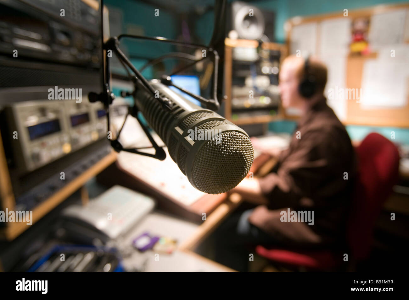 A Radio DJ hosts a radio program from his studio Stock Photo