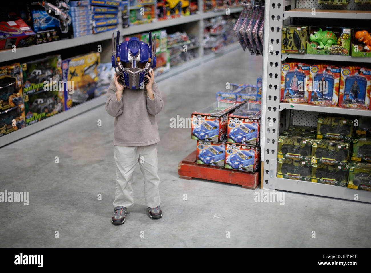 Six year old boy in toystore tries on Optimus Prime robot helmet from the Spielberg movie Transformers - Stock Image