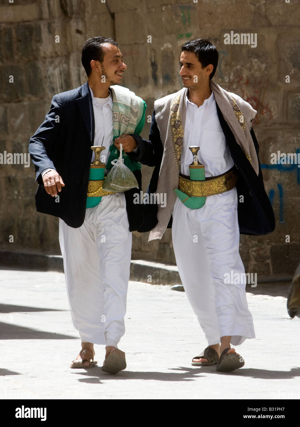 Young Muslim men from Yemen walking through Old Sanaa City wearing their traditional Jambiya daggers - Stock Image