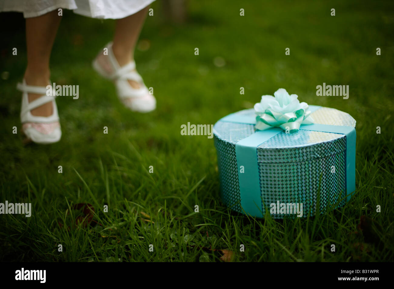 Five year old girl with green box wrapped in ribbon and rose, jumps in the air feet off ground - Stock Image