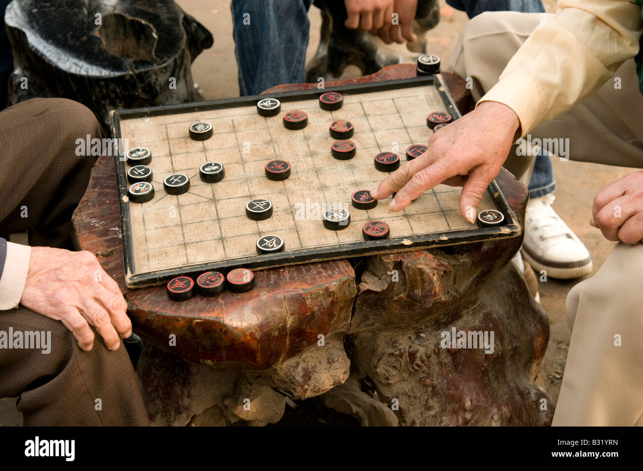 Close up of old male hands on a board game in Hanoi Vietnam played by two elderly Vietnamese men Stock Photo