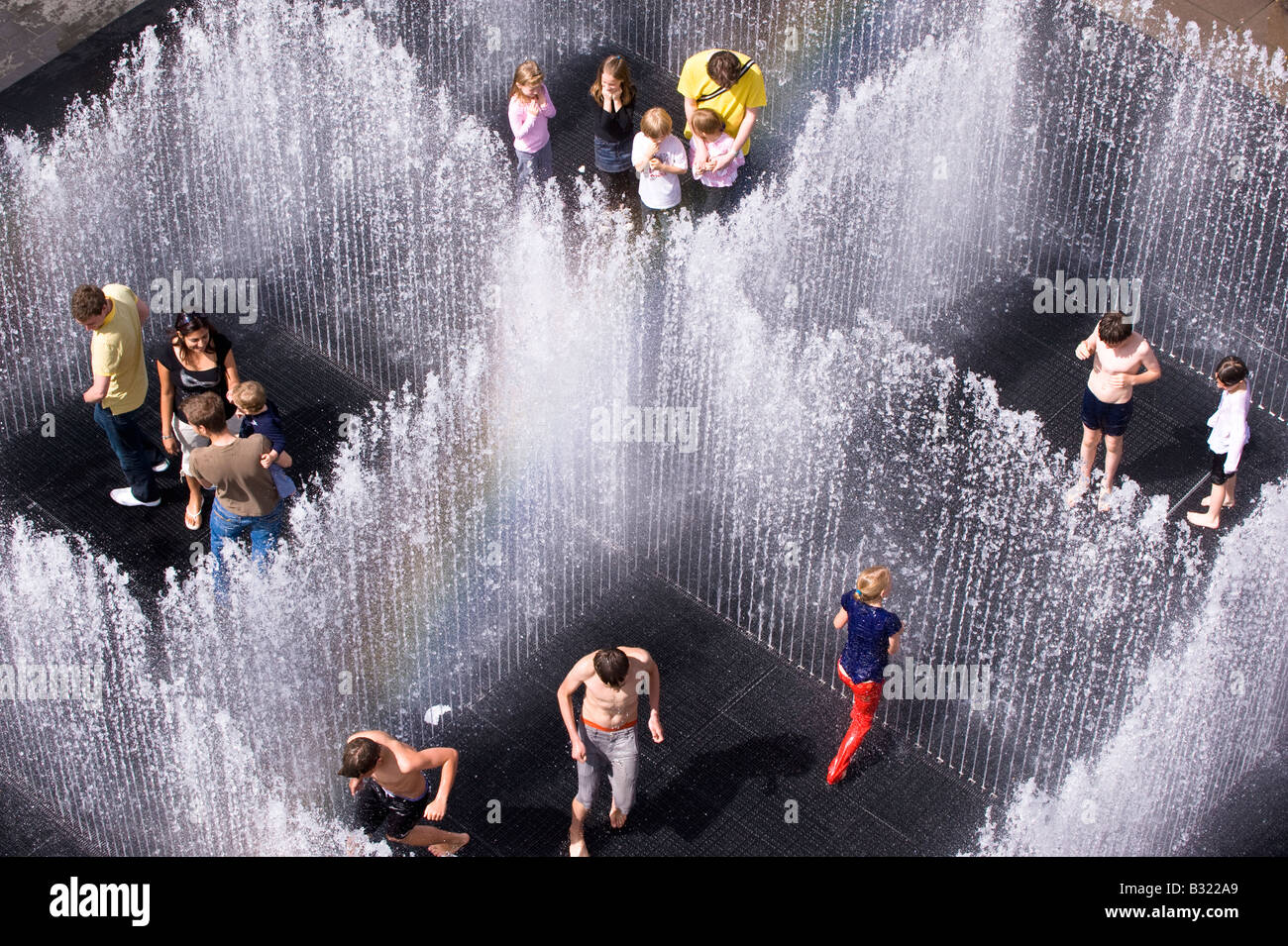 Children enjoy playing in water fountain on hot summer day, Southbak, London, SE1, United Kingdom - Stock Image