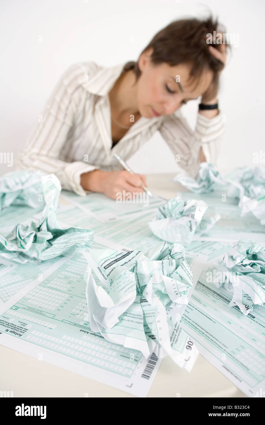 Woman completing her tax declaration after several failed attempts - Stock Image