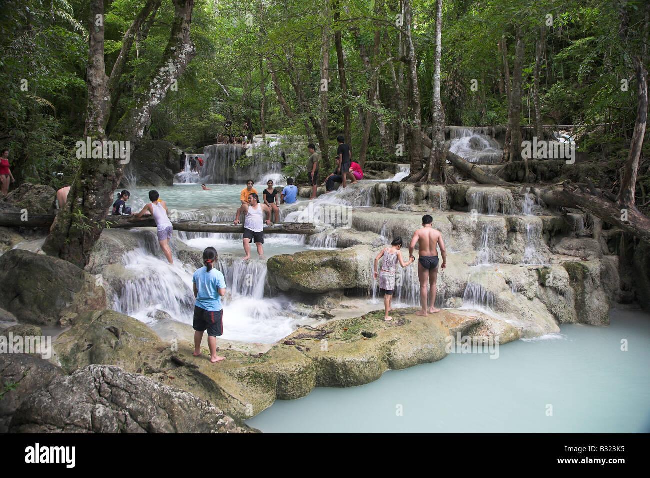 Local familes enjoying the Erawan Falls in Kanchanaburi in Thailand. - Stock Image