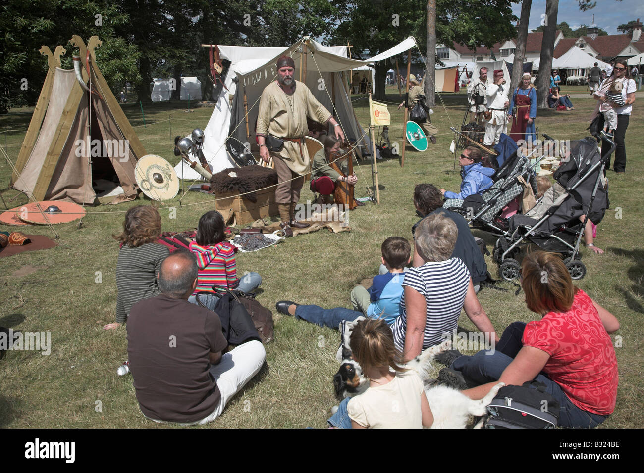 Anglo-Saxon re-enactor talking to an audience sitting on the grass at a Living History re-enactment - Stock Image