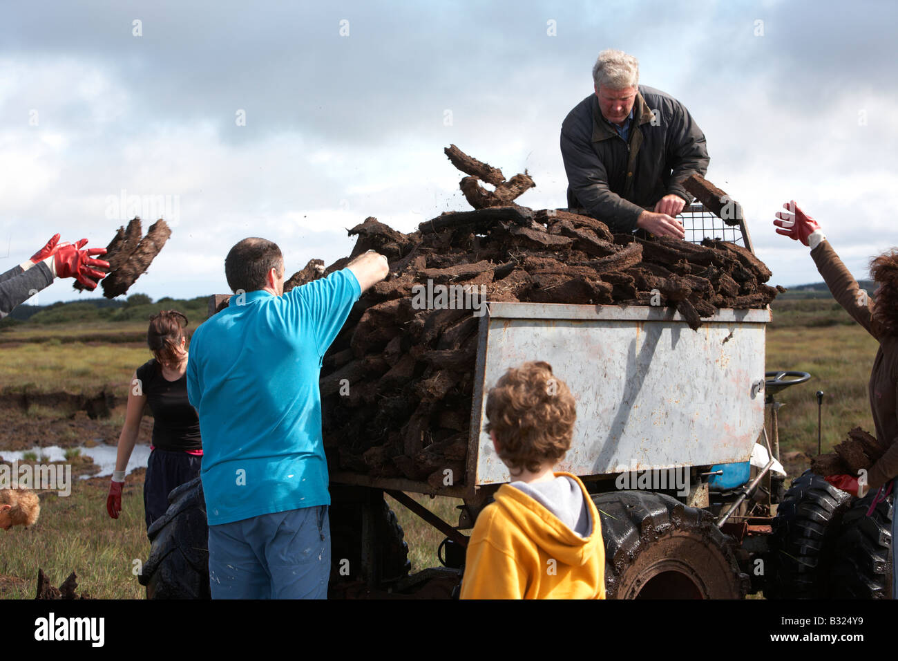 large extended irish family bringing home the turf peat fuel collection on home made transporter in easkey county - Stock Image