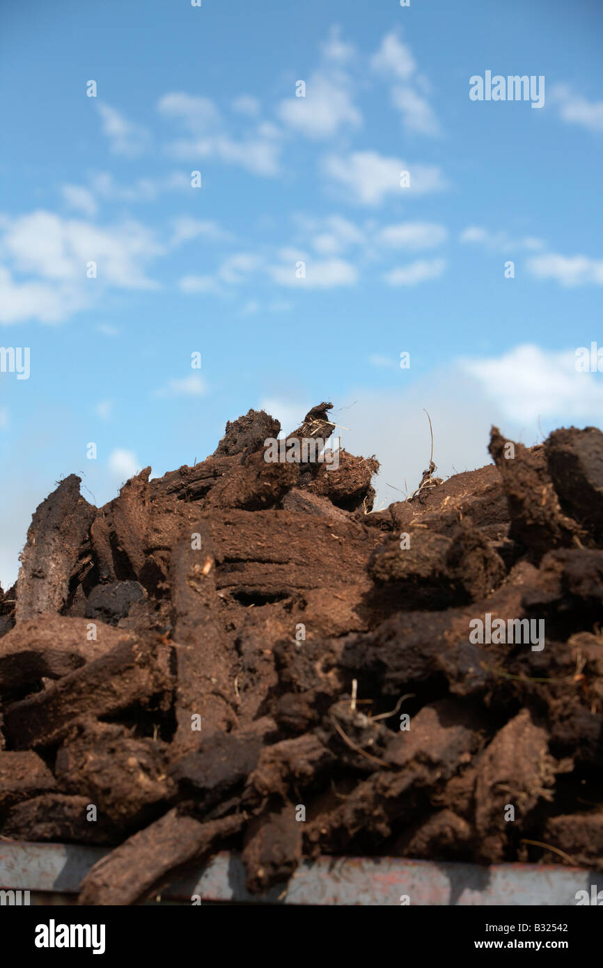 peat turf fuel gathered and loaded into a pile against cloudy blue sky county sligo republic of ireland - Stock Image