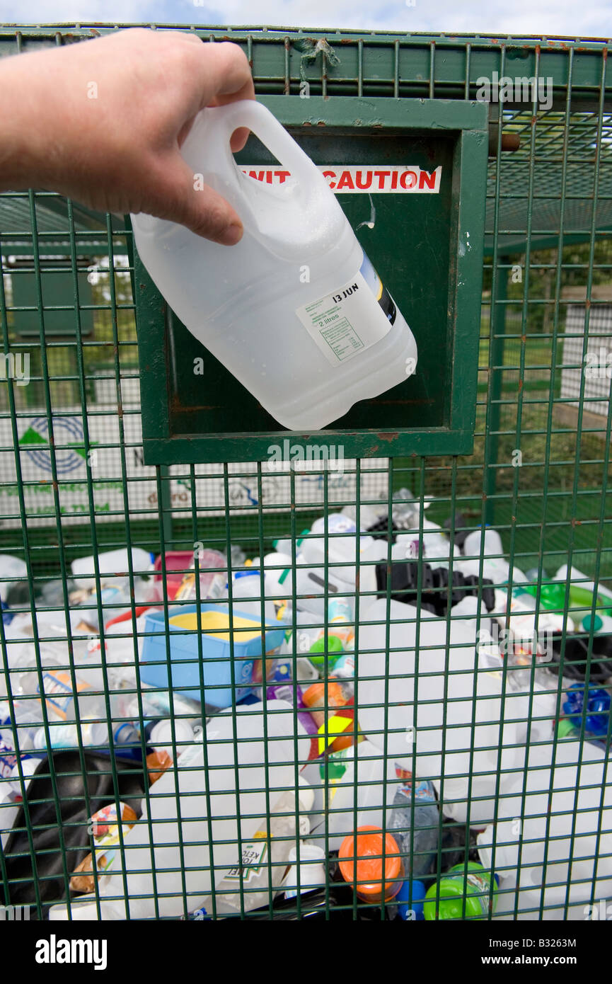 putting waste household plastic into recycling container at recycling point Tebay Cumbria - Stock Image