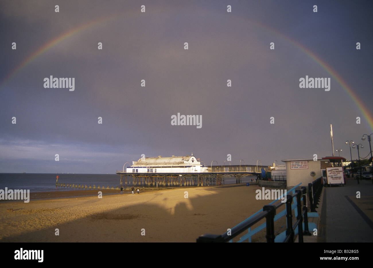 Sea Pier Beach Rainbow in dark stormy cloudy sky CLEETHORPES LINCOLNSHIRE ENGLAND - Stock Image