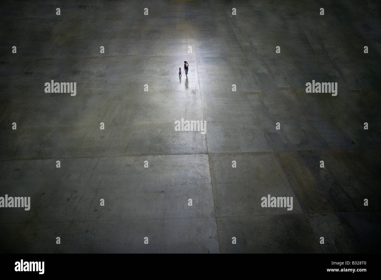 Single woman with her children at the large empty concrete area in darkness - symbol of abandoned mother - Stock Image
