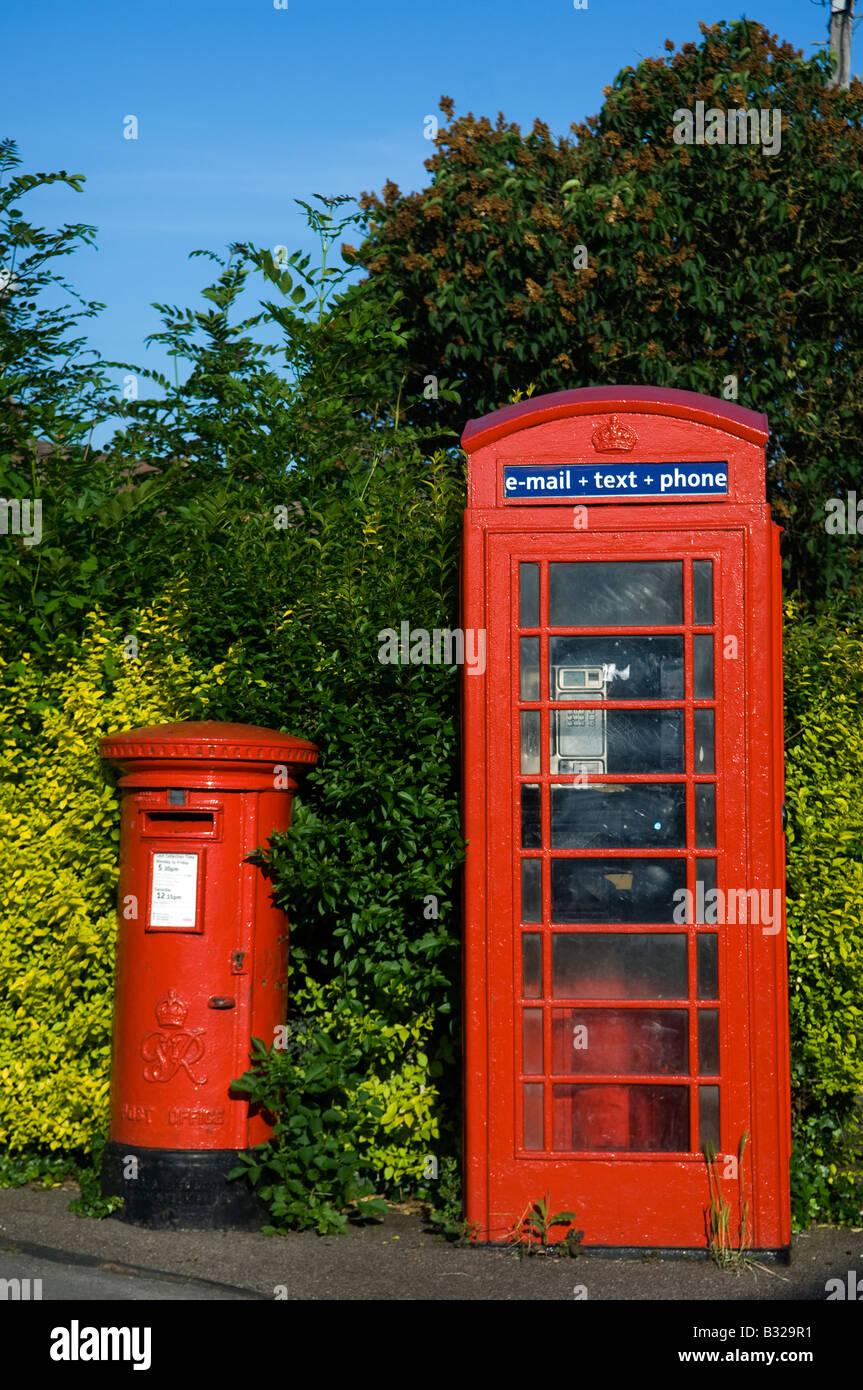 Traditional red George V pillar post box beside a classic red K6 telephone kiosk - Stock Image