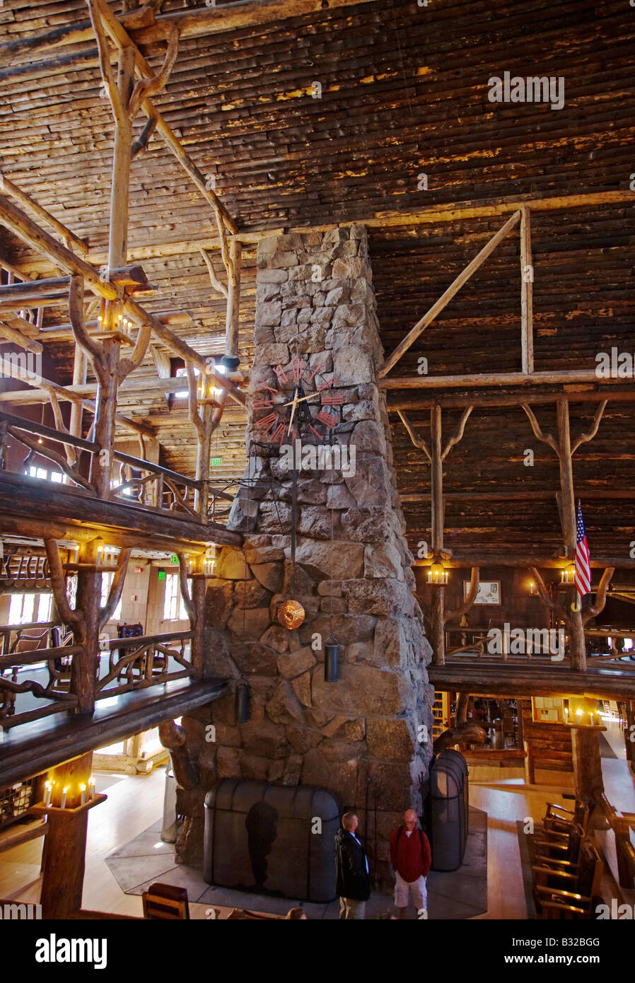 STONE FIREPLACE of the log constructed interior of historic OLD FAITHFUL INN completed 1904 YELLOWSTONE NATIONAL - Stock Image