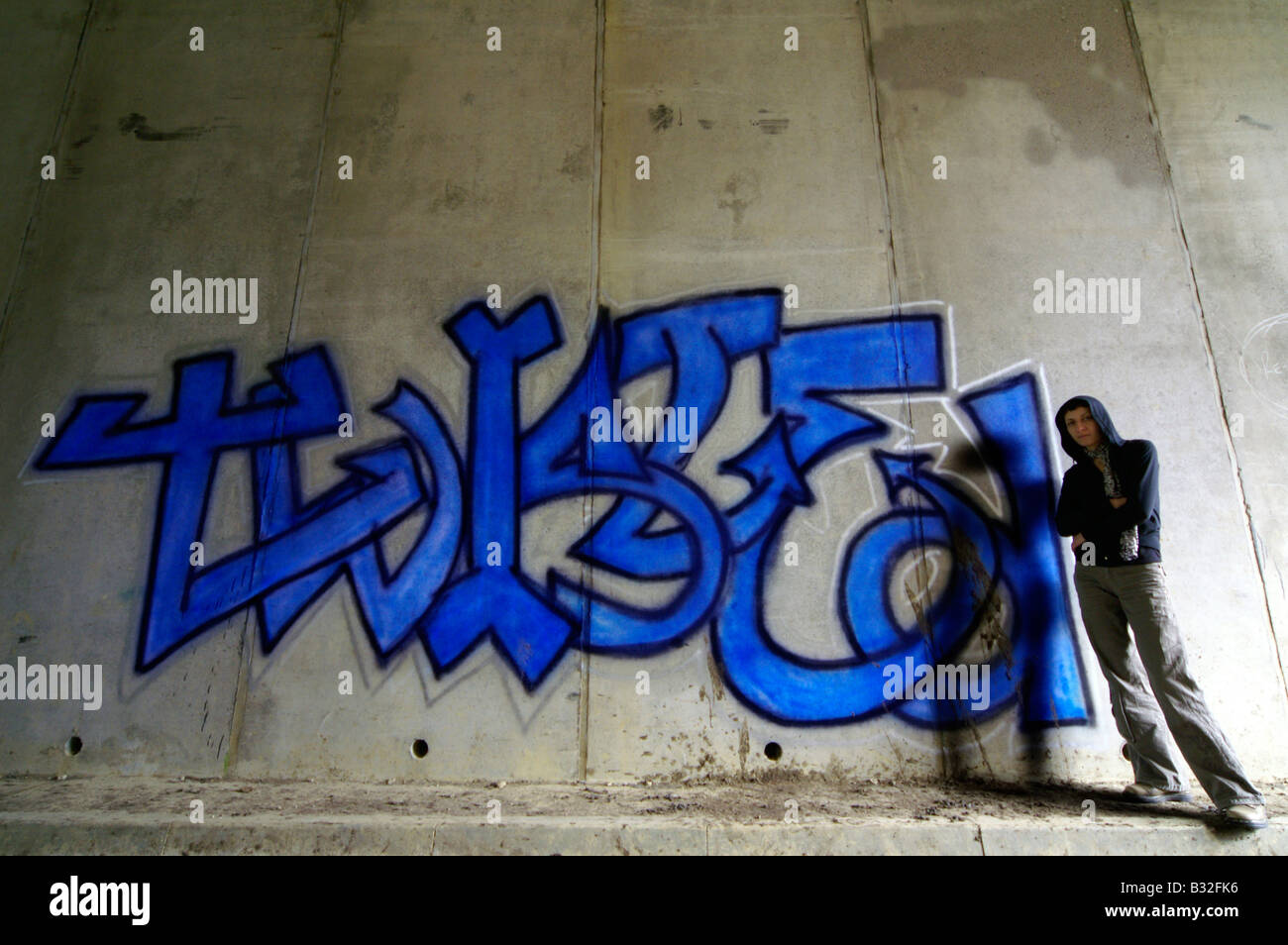 Hooded girl standing next to her graffiti on the wall in the tunnel, South Bank, London - Stock Image