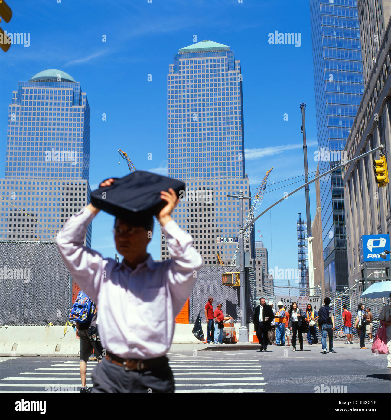 A man walking shading his face from the summer heat and glare with his laptop on Vesey Street near Ground Zero in - Stock Image