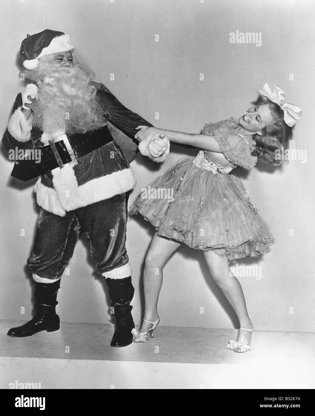 Woman trying to dance with Santa Claus - Stock Image