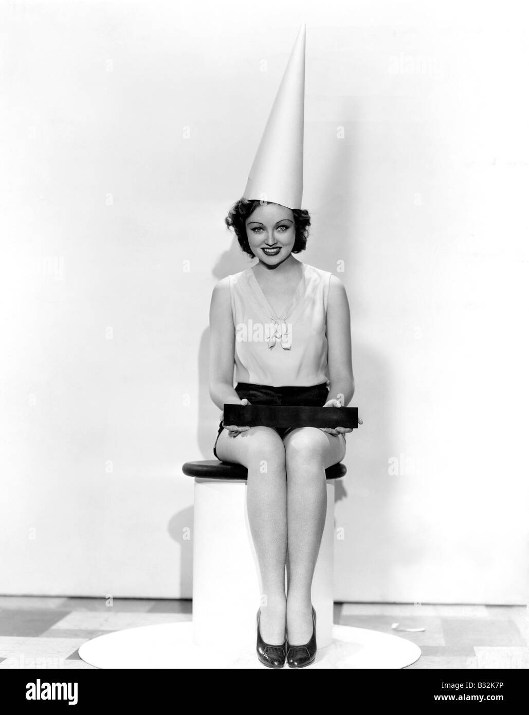 Portrait of woman with April Fool sign wearing dunce cap - Stock Image