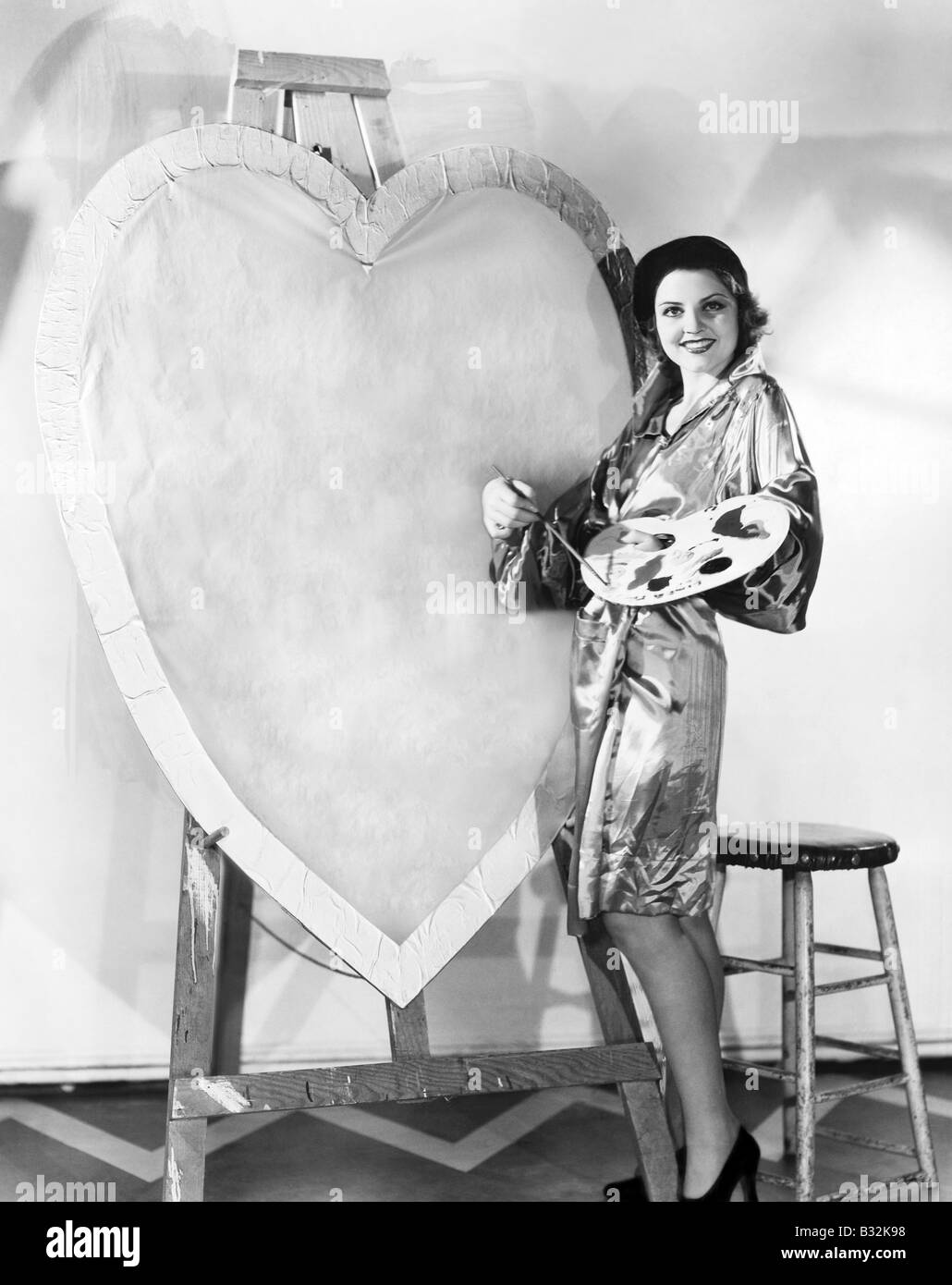 Woman painting huge valentine - Stock Image