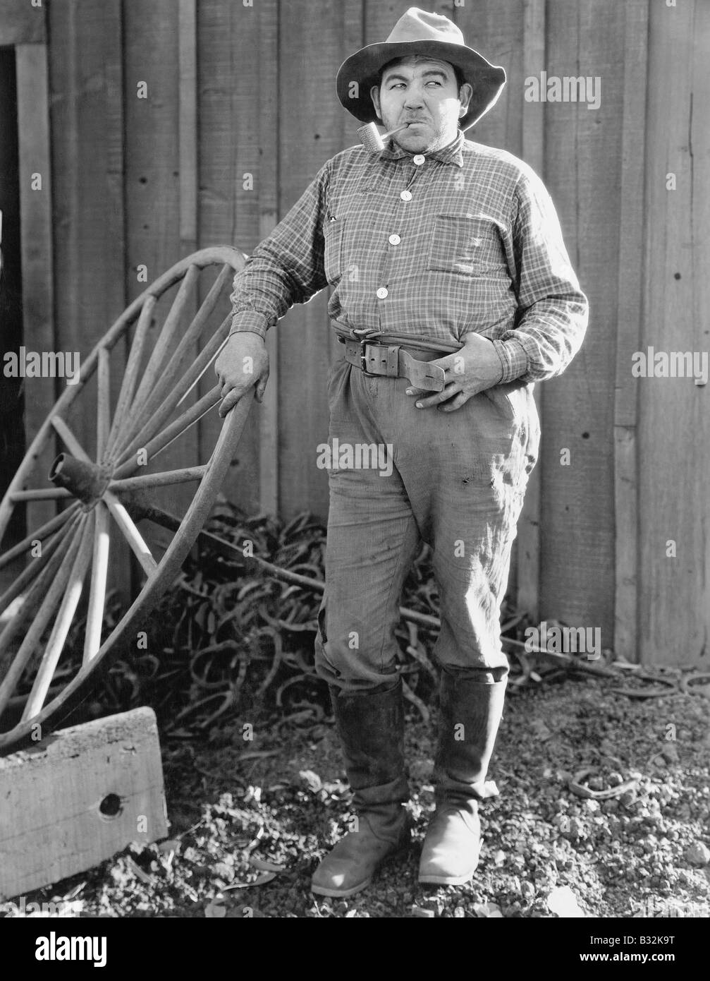 Portrait of man with pipe and wooden wheel - Stock Image