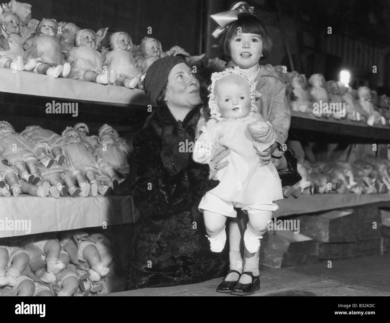 Mother and daughter with shelves of dolls - Stock Image