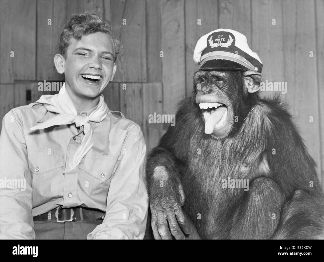 Laughing boy scout and monkey wearing hat - Stock Image