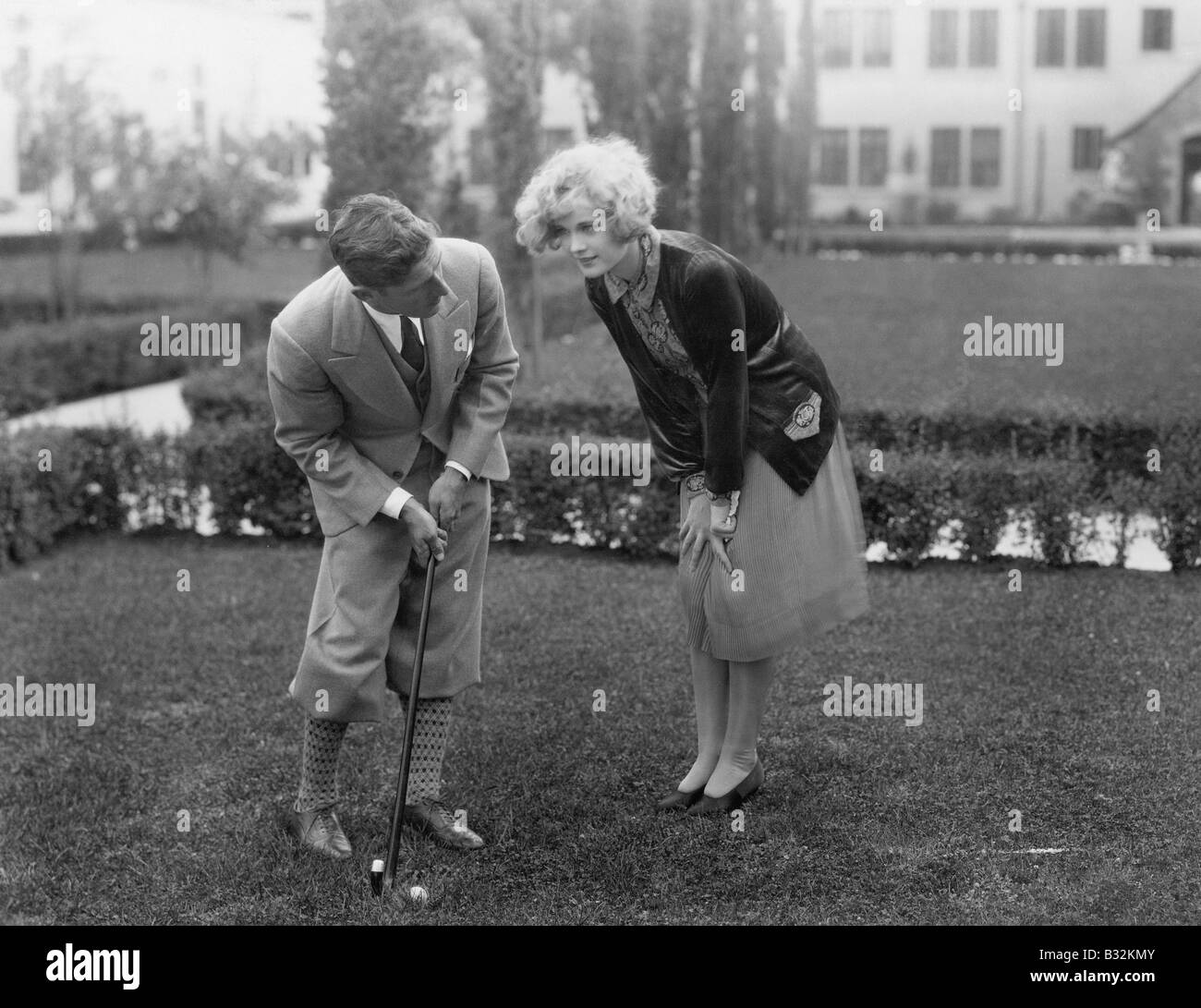 Man talking to woman while golfing - Stock Image