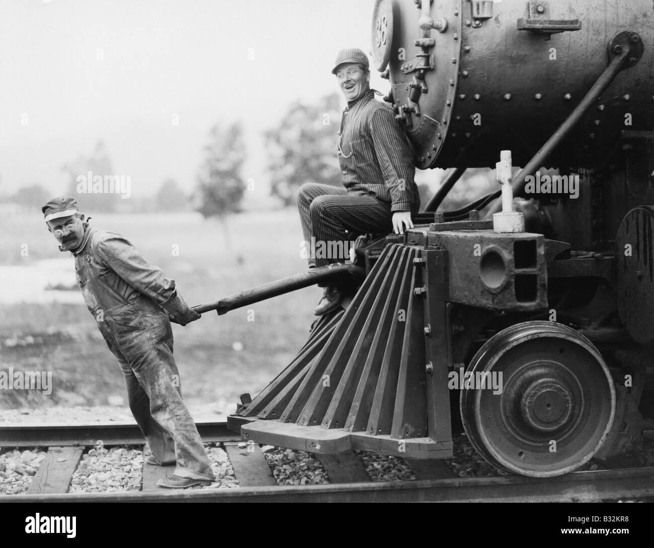 Engineers pulling train engine - Stock Image