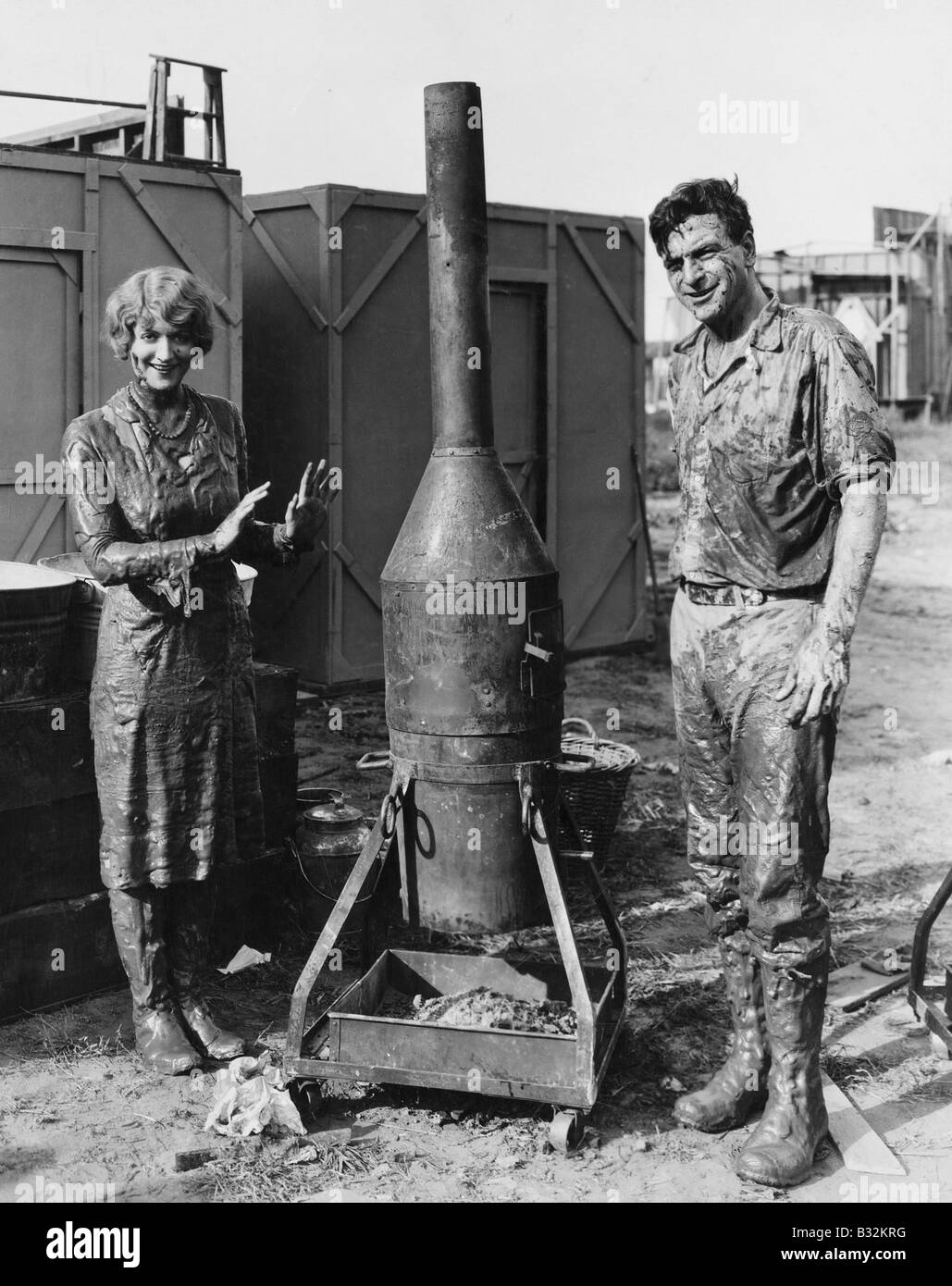 Mud covered couple with portable stove - Stock Image