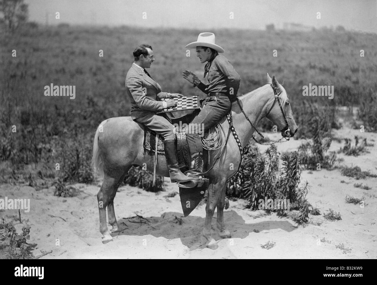 Cowboy and businessman playing checkers on horseback - Stock Image