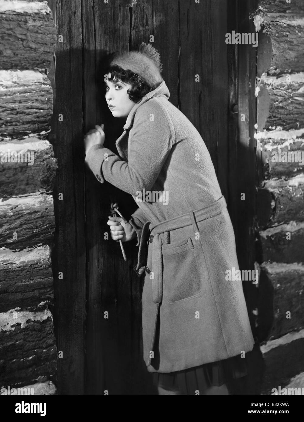 Woman knocking on cabin door - Stock Image