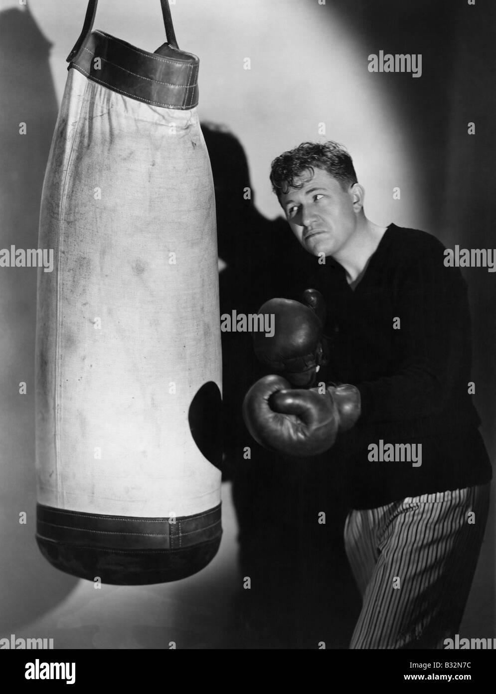 Boxer using punching bag - Stock Image