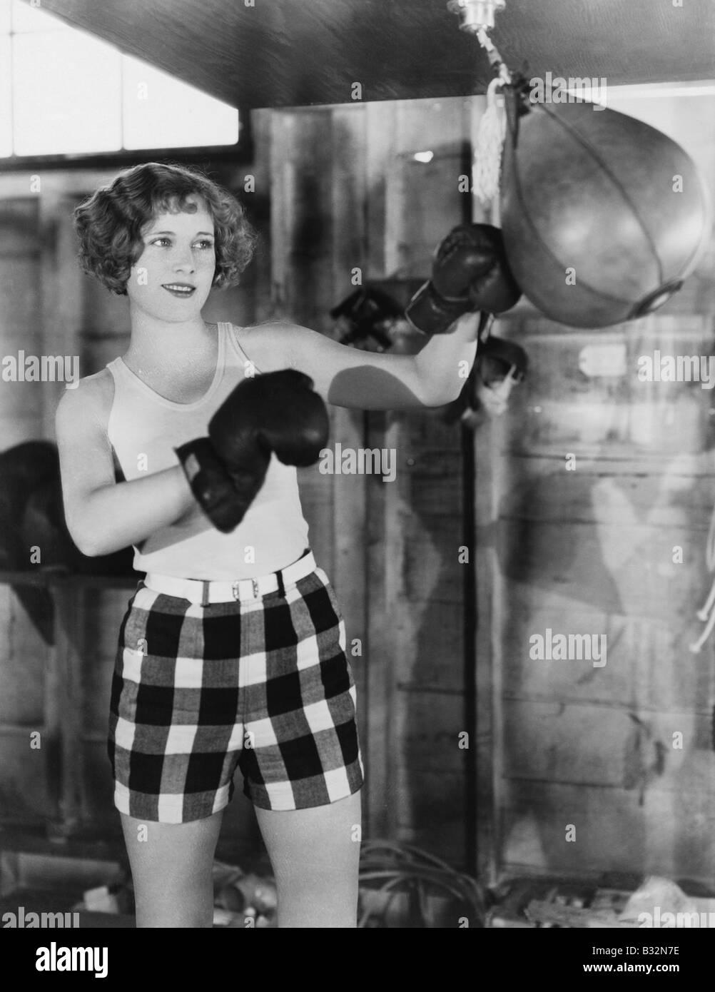 Female boxer using punching bag - Stock Image