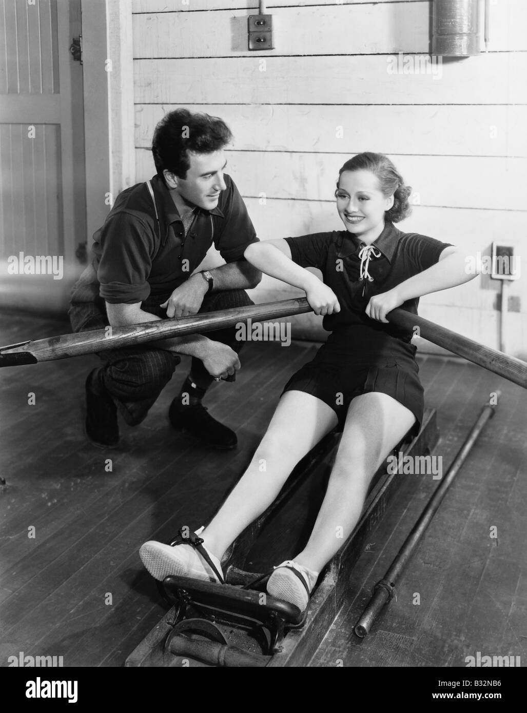 Man with woman using rowing machine - Stock Image