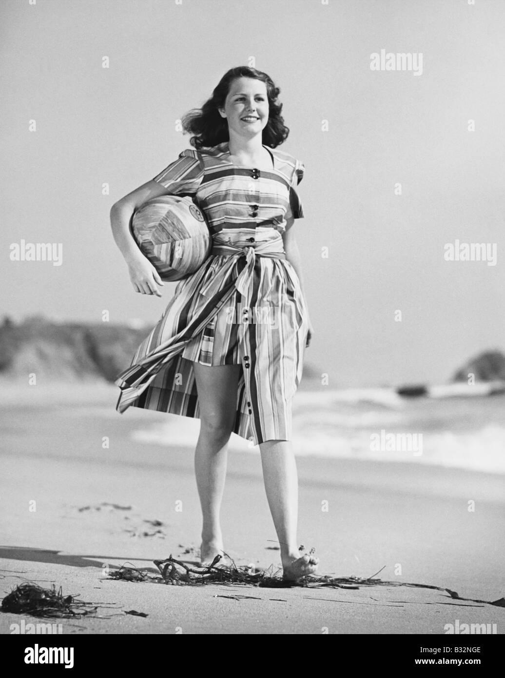 Woman walking on beach carrying ball Stock Photo